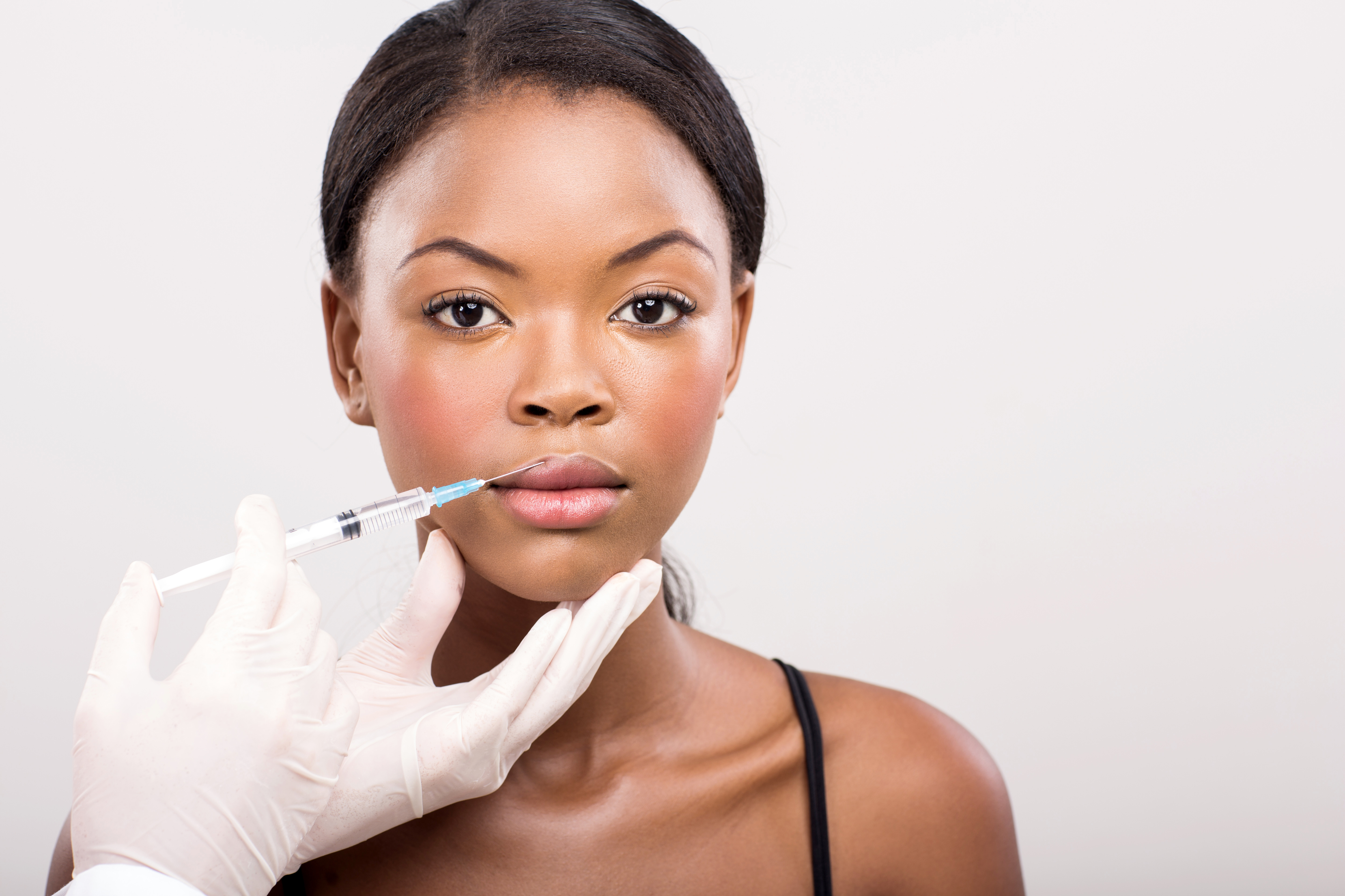 pretty african girl receiving cosmetic injection on her lips